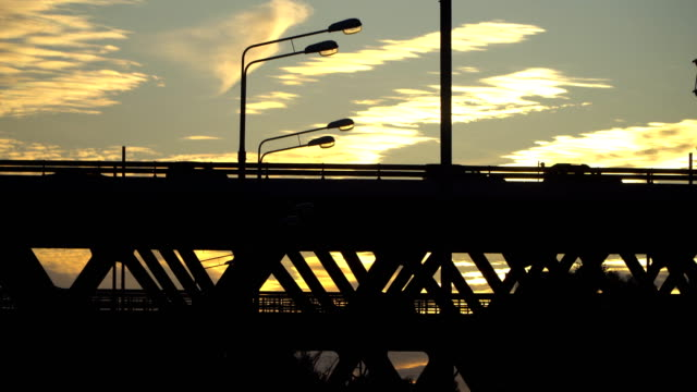silhouette of the steel bridge and vehicles moving on it video
