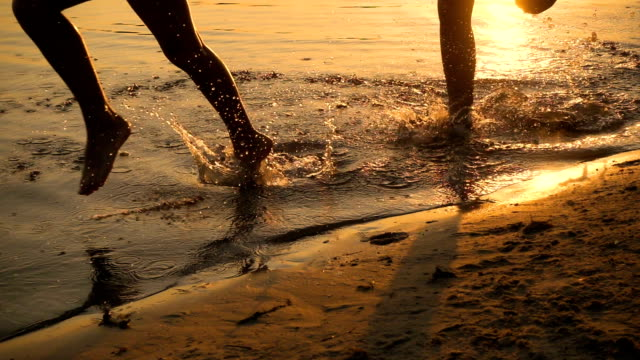 Silhouette of two kids running to beach at sunset video