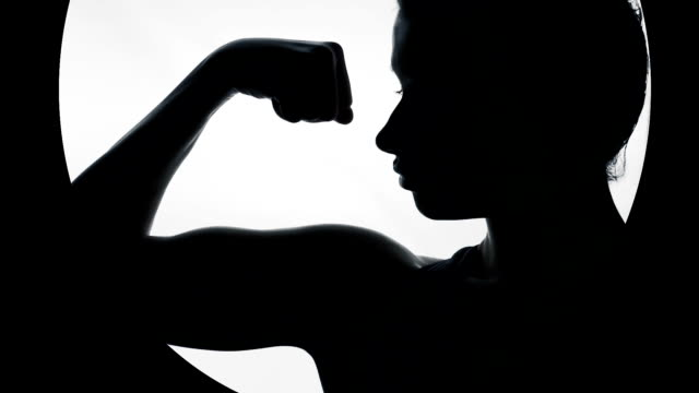 Silhouette of woman boasting of strong biceps, demonstrating feminine strength video