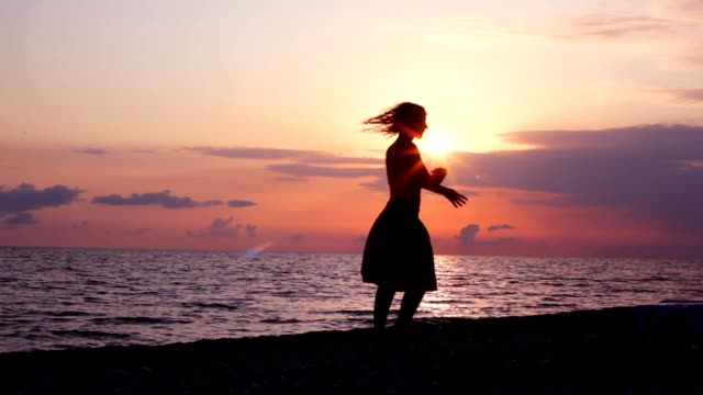 Silhouette of woman dancing on beach video