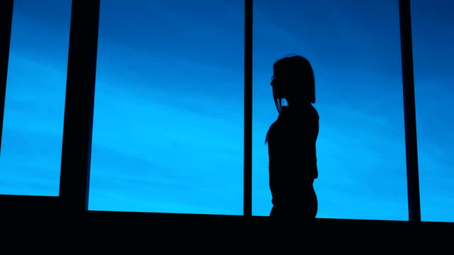 Silhouette of woman in office. Silhouette of unrecognizable woman standing at window in office in the evening video