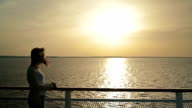 Silhouette of woman on deck of cruise ship at sunrise video
