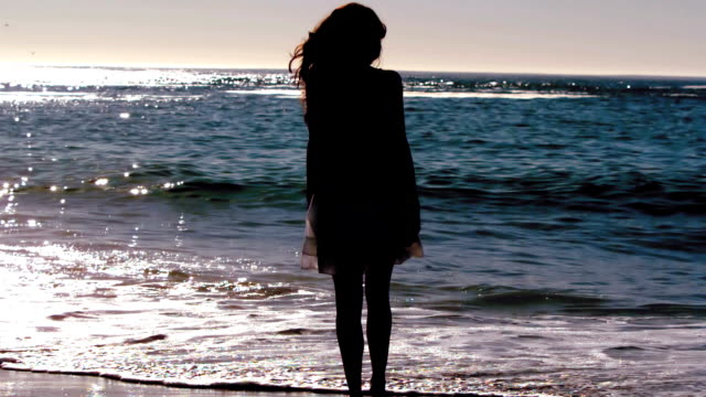 Silhouette of woman skipping on the beach video