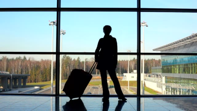 Silhouette of woman with travel luggage stands against window video
