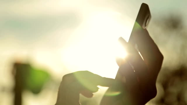 Silhouette of woman's hands with smart phone at sunset video