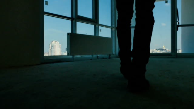 Silhouette of young businessman near the window video