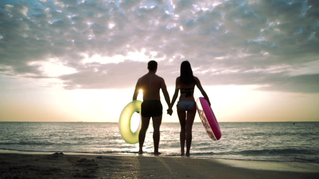 Silhouette of young couple on the beach with rubber rings during sunset video