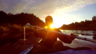 Silhouette of young happy man paddling kayak at sunset, slow-mo video