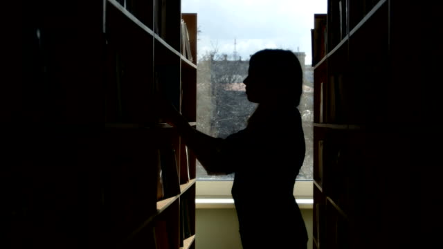 Silhouette of  young student reading a book in a library video