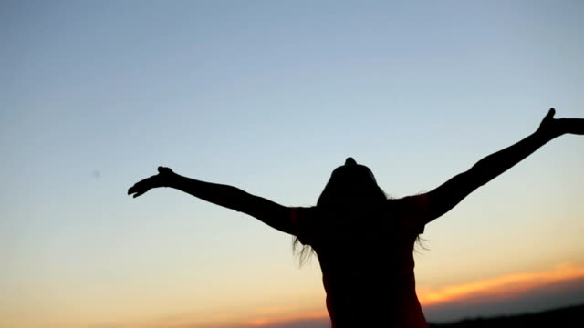 Silhouette of young woman raising hands to sun at sunset. Moment of freedom and happiness. Young woman meditates on the bridge with city landscape background video