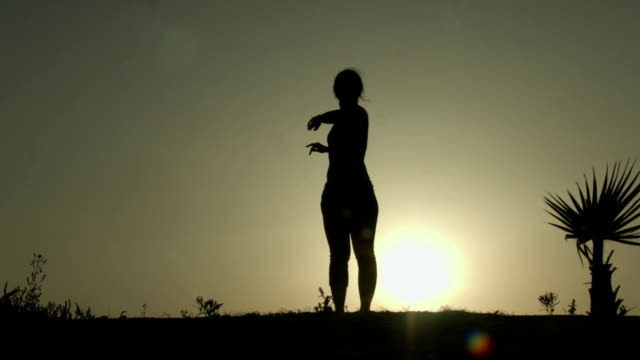 Silhouette of young woman stretching before doing exercises early in video