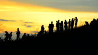 Silhouette scene of people on a mountain peak. video