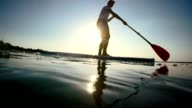 SLO MO Silhouette stand-up paddleboarding on the lake video