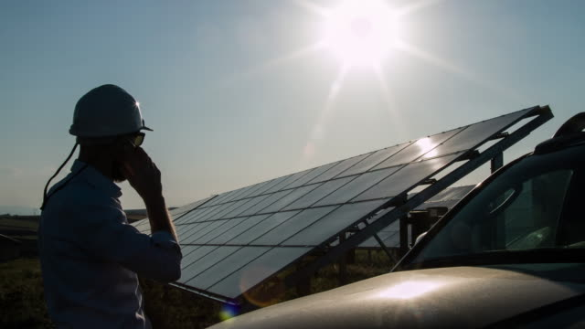Silhouette Technician talking by phone at Solar Power Station video