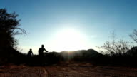 Silhouette Two People Mountain Bike Riding At Sunset video