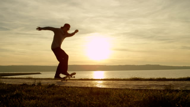SLOW MOTION: Silhouetted skater jumping and doing a flip tricks against the sun video