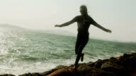 A silhouetted young woman jumps from rock to rock by the water. video
