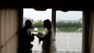 Silhouettes just married couple near big window in rainy day video
