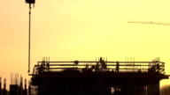 Silhouettes of construction workers against orange sky. FullHD telephoto lens shot video