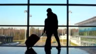 Silhouettes of couple stands against window at airport video