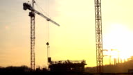 Silhouettes of crane transferring concrete plate and construction workers. FullHD video