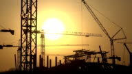 Silhouettes of cranes and construction site against orange sunset. FullHD video video