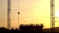 Silhouettes of cranes and construction site workers against orange sunset. FullHD video