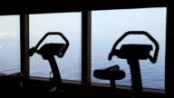 Silhouettes of empty exercise bicycles in gym video