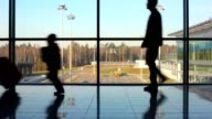 Silhouettes of family hurry to aircraft against window video