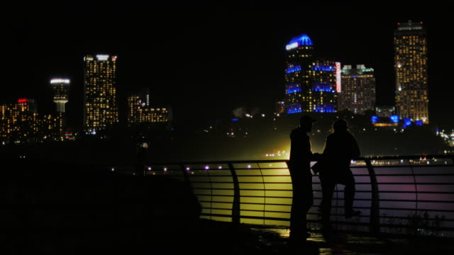 Silhouettes of men and women against the background of skyscrapers in a night city. Communicate, full-length, free space for titles video