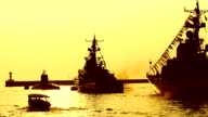 silhouettes of missile boats and a submarine in the bay at sunset video