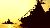 silhouettes of modern warships at sunset video