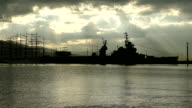 silhouettes of old ships at the pier on the background of dawn video