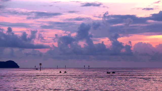Silhouettes of people and boats at sunset. video