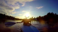 Silhouettes of people boating at sunset, traveling, slowmotion video