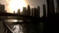 Silhouettes of two boats passing under the bridge on the waterfront of Dubai Marina at sunset video