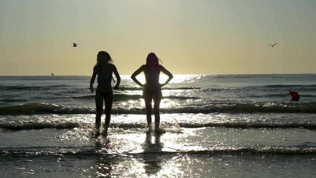 Silhouettes of two women coming out of the sea in slow motion video