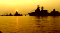 silhouettes of warships at sunset video
