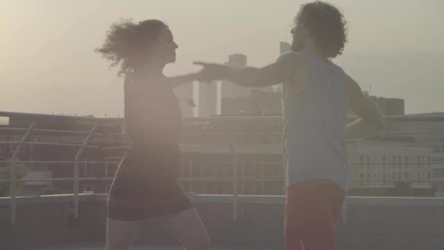 Silhouettes of young couple dancing on sunset video