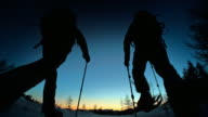 SLO MO LD silhouettes snowshoeing into sunset on mountain top video