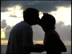 Silhoutted Couple Kissing in front of Sunrise / Sunset video