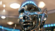 Silver color, mirror surfaces of face humanoid ( human ) reflects lights video