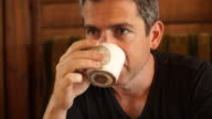 Silver-haired middle-aged Caucasian is drinking coffee video