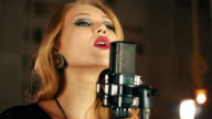 Singer with bright make up perform on stage at microphone. Jazz. Earrings video