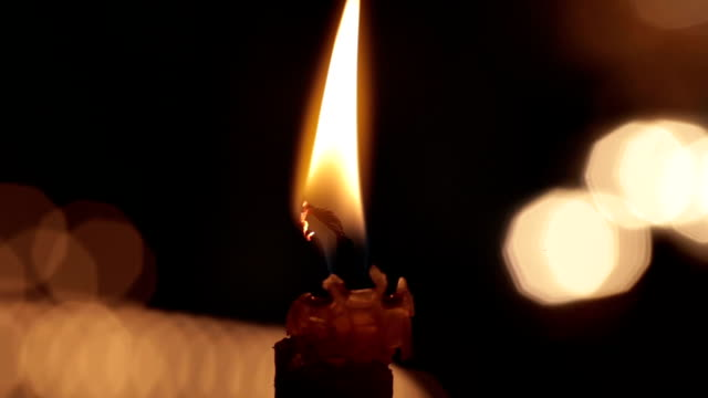 Single candle with flame fire dripping wax in church cathedral. Black macro video