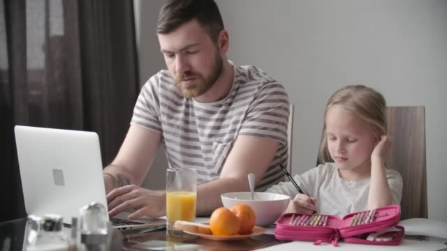 Single father working at home with daughter nearby video