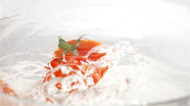 Single red ripe tomato with green leaves falls under water video