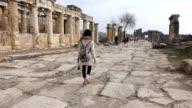 single woman is walking inside the Hierapolis video
