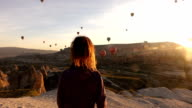single woman is walking while watching hot air balloons in Cappadocia video