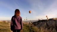 single woman walking while watching hot air balloons in Cappadocia video